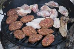 La carne cruda y las alas de pollo frescas están asando a la parrilla en una barbacoa Fotografía de archivo