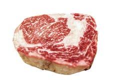 La carne de vaca cruda del ribeye miente en un fondo blanco Carne veteada imagen de archivo