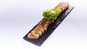 La carne di maiale affettata rotola con le erbe sul piatto nero della roccia fotografia stock libera da diritti