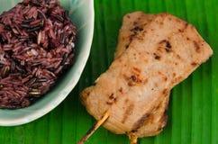 La carne di maiale arrostita con il bastone di bambù ed il riso appiccicoso nero sulla banana coprono di foglie Fotografie Stock Libere da Diritti