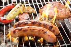 La carne di maiale della salsiccia e la bistecca di taglio su un BBQ ardente grigliano Immagini Stock