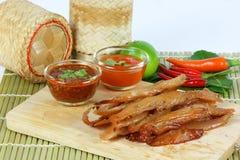 La carne di maiale secca ha fritto con salsa ketchup e la salsa di peperoncini rossi su vecchio corteggia Immagine Stock