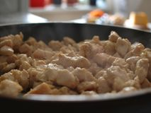 La carne di pollo è fritta in una padella immagine stock