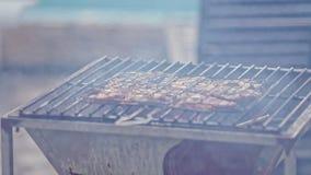 La carne fresca asa en el fuego abierto de la rejilla del brasero del metal metrajes