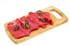 La carne fresca cruda ha affettato la i a bordo con rosmarino Fotografie Stock