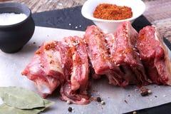 La carne fresca cruda, le costole crude di manzo o dell'agnello con pepe, aglio, sale e le spezie su fondo di pietra scuro, aspet fotografie stock libere da diritti