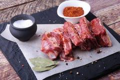 La carne fresca cruda, le costole crude di manzo o dell'agnello con pepe, aglio, sale e le spezie su fondo di pietra scuro, aspet fotografia stock libera da diritti