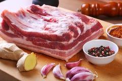 La carne fresca cruda, le costole crude di manzo o dell'agnello con pepe, aglio, sale e le spezie su fondo di pietra scuro, aspet immagine stock libera da diritti