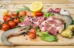 La carne fresca, i frutti di mare e le verdure sulla cucina imbarcano Immagini Stock Libere da Diritti