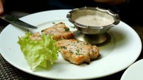 La carne fritta è tagliata con un coltello, per pungere su una forcella, è immersa in salsa ed è mangiata stock footage