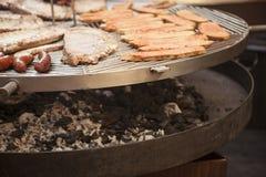 La carne gastrónoma junta las piezas de las costillas de cerdo, salchichas, en una parrilla grande Imágenes de archivo libres de regalías