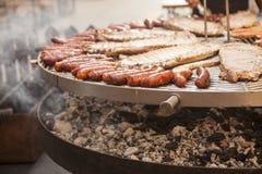 La carne gastronomica collega le costole di carne di maiale, salsiccie, su una grande griglia Fotografie Stock