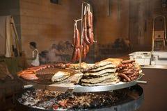 La carne gastronomica collega le costole di carne di maiale, salsiccie, su una grande griglia Fotografia Stock Libera da Diritti