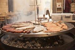 La carne gastronomica collega le costole di carne di maiale, salsiccie, su una grande griglia Immagini Stock