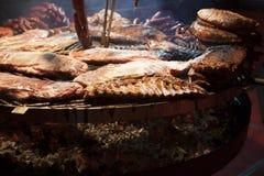 La carne gastronomica collega le costole di carne di maiale, salsiccie, su una grande griglia Fotografia Stock