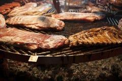 La carne gastronomica collega le costole di carne di maiale, salsiccie, su una grande griglia Immagini Stock Libere da Diritti