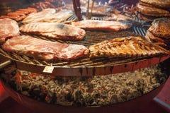 La carne gastronomica collega le costole di carne di maiale, salsiccie, su una grande griglia Immagine Stock Libera da Diritti