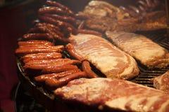 La carne gastronomica collega le costole di carne di maiale, salsiccie, su una grande griglia Immagine Stock