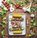 La carne, le verdure e gli spiedi saporiti del cereale in erbe marinano con condimento fresco e spazzola di unto per la griglia s immagini stock