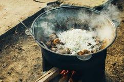 La carne se cocina en una caldera en la calle Imágenes de archivo libres de regalías