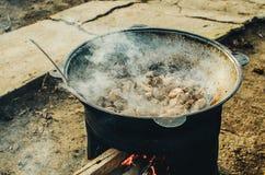 La carne se cocina en una caldera en la calle Imagen de archivo libre de regalías