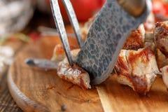 La carne succosa ha cucinato su un fuoco aperto che comincia a tagliare con un coltello e una forcella originali Fotografie Stock Libere da Diritti