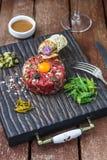 La carne a la tártara sirvió con las alcaparras, los pepinos conservados en vinagre y la cebolla tajada Imágenes de archivo libres de regalías