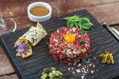 La carne a la tártara sirvió con la yema de huevo cruda de codornices y el otro ingrediente tartare Plato de la carne Fotos de archivo libres de regalías