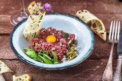 La carne a la tártara sirvió con la yema de huevo cruda de codornices y el otro ingrediente tartare Plato de la carne Fotos de archivo