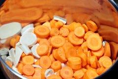 La carota ed il prezzemolo hanno tagliato dentro un POT dell'acciaio inossidabile immagini stock