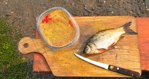 La carpe de poissons se trouve sur la planche à découper Images libres de droits