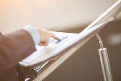 La carpeta con el hombre de negocios de las cartas y de los gráficos señala su finger al punto deseado del gráfico superior Fotos de archivo libres de regalías