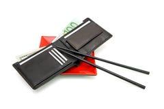 La carpeta y el dinero en la placa con los palillos aislaron Imagen de archivo libre de regalías