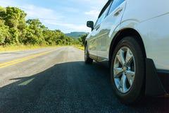 La carretera de asfalto con los coches que pasan a través del bosque y los mountens ajardinan en día de verano Efecto entonado Foto de archivo libre de regalías
