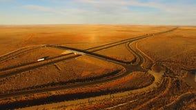 La carretera de oro de la puesta del sol corta a través paisaje del desierto almacen de metraje de vídeo