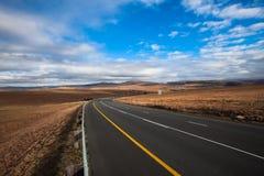 La carretera pone en contraste las colinas secas de los paisajes Fotografía de archivo