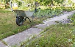 La carriola del giardino sta vicino al percorso concreto nel giardino dell'estate Fotografia Stock