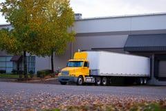 La carrozza ed il rimorchio di giallo del camion dei semi hanno parcheggiato al bacino per scaricare Immagine Stock Libera da Diritti