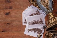 La carta con l'immagine dei treni e di vecchia lampada di cherosene su un fondo di legno Fotografia Stock