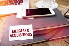La carta con le fusioni & le acquisizioni mandano un sms a sul desktop dell'ufficio Immagine Stock