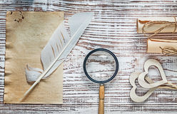 La carta d'annata dello strato rotola i cuori che di legno della piuma la lente sopra corteggia Immagine Stock