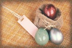 La carta d'annata struttura la decorazione di pasqua, le uova variopinte e l'etichetta in bianco Fotografie Stock