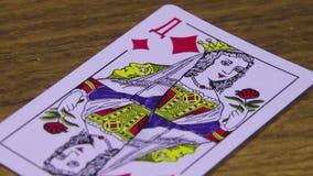 La carta da gioco gira su una Tabella di legno stock footage