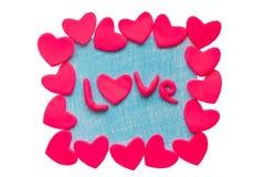 La carta del biglietto di S. Valentino con i cuori dell'argilla e la parola amano su un fondo bianco Fotografia Stock