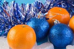 La carta del nuovo anno con le palle blu, fiocchi di neve bianchi spuma, abbronzatura arancio Fotografie Stock