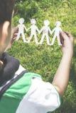 La carta della tenuta del bambino ha fatto le figure della gente Fotografia Stock