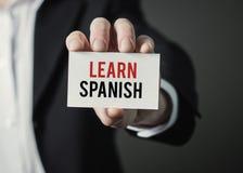 La carta della tenuta dell'uomo d'affari con testo impara lo Spagnolo Fotografie Stock