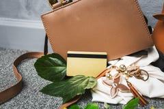 La carta di credito dorata sopra gli accessori marroni della donna della borsa per va a SH Fotografia Stock Libera da Diritti