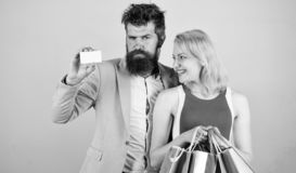 La carta di credito e la ragazza barbute della tenuta dei pantaloni a vita bassa dell'uomo godono di di comperare Chieda all'uomo immagini stock