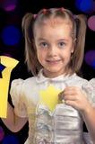 La carta felice di taglio della bambina calcola per il Natale contro fondo nero con le luci vaghe Fotografia Stock
